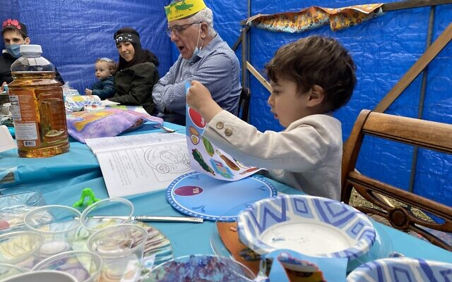 "SEDER IN A SUKKAH: Howard Jacob and Helene Jacob of Fresh Meadows, members of the Hillcrest Jewish Center, held what they think may be the first-ever Passover Seder in a sukkah. The couple, who completed their COVID-19 vaccinations in February, left the thatched roof off of the booth to improve circulation and invited their two married daughters and their husbands, each with two children, ages ranging from one to five. ""I thought it was a good way to get our family together for Pesach and address the concerns our children had re: COVID,"" Howard explained. Above, from left, Andrew Zizmor, Eli Zizmor, Ariela Zizmor, Howard  Jacob  and Sammy Rehr. (Courtesy Howard Jacob)"