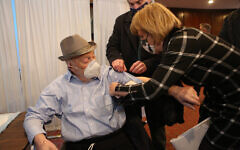 Gerontologist/RN Cathy Byrne administers the Covid-19 vaccine to Jakob Rybsztajn as State Senator Todd Kaminsky lends a hand at the Marion & Aaron Gural JCC in Cedarhurst, Feb. 28, 2021. (Gural)