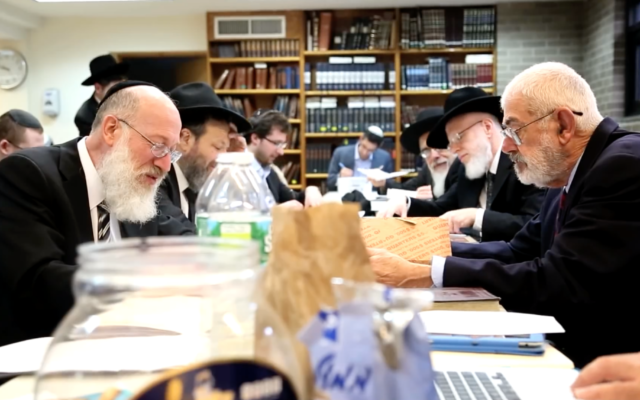 Rabbi Mordechai Willig, left, executes the 2015 sale of hametz to John J. Brown, right. Dozens of NY rabbis depended on Brown to buy their congregations' leavened products before  Passover. (Josh Weinberg/screenshot from YouTube)
