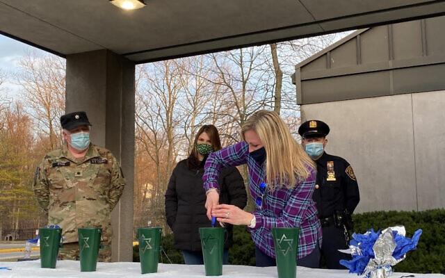LIGHT IN THE DARKNESS: Renya Glab, a nursery school teacher at the JCC of Mid-Westchester in Scarsdale, lights a memorial candle at an outdoor ceremony marking the anniversary of New York's first recorded case of COVID-19, March 12, 2021. Behind her are, left to right, National Guard Lieutenant Colonel Ryan, coronavirus victim Cathy Klein's daughter Lauren Klein and New Rochelle Detective Francesco Provenzale. (JCCMW)