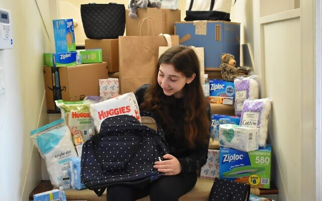 Ariel Kirman with some of the supplies she distributes to refugee mothers through her nonprofit, Diaper Essentials for New Americans, or DENA. (Courtesy)