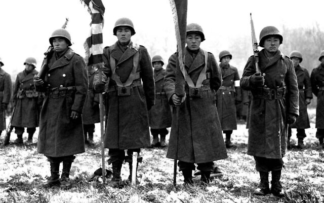 Color guards and color bearers of the Japanese-American 442d Combat Team stand at attention while their citations are read at a ceremony in the Bruyeres area of France, where many of their comrades fell, Nov. 12, 1944. (U.S. Army Signal Corps)