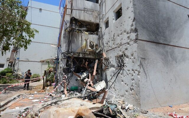Residents examine the damage at their home after it was hit the day before by a rocket fired from the Gaza Strip, in the southern Israeli city of Ashdod, May 18, 2021. (Avi Roccah/Flash90)