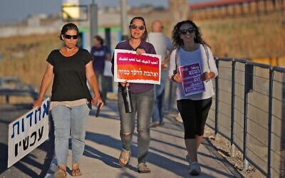 """Jewish and Arab women walk in a demonstration for coexistence in northern Israel on May 11, 2021. The sign in the middle says """"Love your neighbor as yourself."""" (Jalaa Marey/AFP)"""