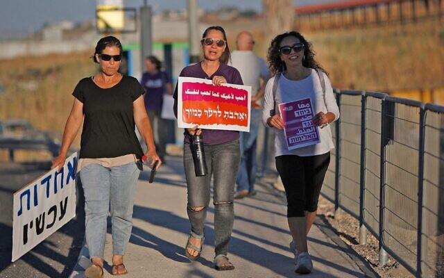 "Jewish and Arab women walk in a demonstration for coexistence in northern Israel on May 11, 2021. The sign in the middle says ""Love your neighbor as yourself."" (Jalaa Marey/AFP)"