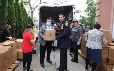 SPIRIT IN ACTION: The Staten Island Council of Jewish Organizations dedicated a day of kindness in memory of the 45 victims of the Meron Lag B'Omer tragedy, with a food distribution at the Aur Torah Sephardic Minyan of Staten Island. Above, COJO president Mendy Mirocznik and Inspector Richard Taylor of the NYPD Community Affairs Bureau load food packages, May 5, 2021. (Courtesy COJO)
