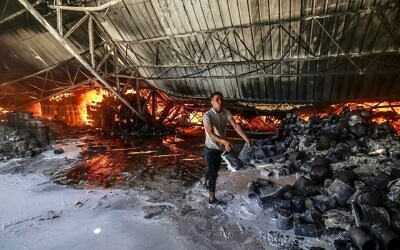 Firefighters attempt to extinguish a fire at a warehouse that was hit during an Israeli airstrike in Rafah, in the southern Gaza Strip, on May 18, 2021. (Abed Rahim Khatib/Flash90)
