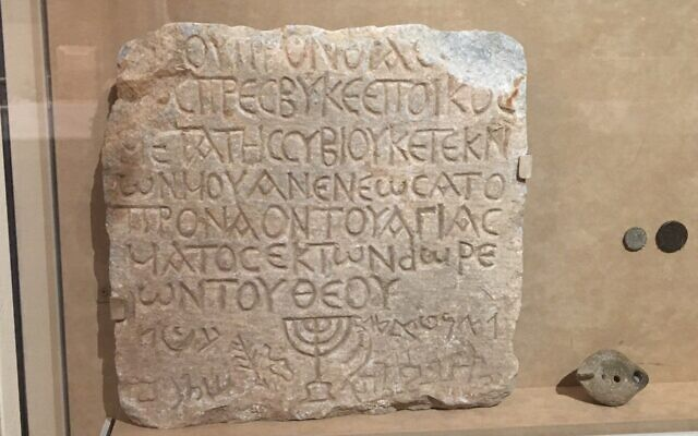 A marble plaque recording a donation to a Roman synagogue is in The Metropolitan Museum of Art, next to the staircase which is lined with the the names of the people who gave donations to the museum. (Jewish Week)