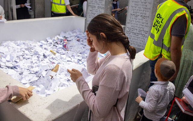 OF BLESSED MEMORY: A young woman reads a prayer she wrote in honor of the 27th anniversary of the passing of the Lubavitcher Rebbe, Rabbi Menachem Mendel Schneerson, on June 13, 2021 at Montefiore Cemetery in Queens. (Photo by Alex Kent/Getty Images)
