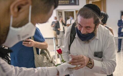 WELCOME: Israeli tourists receive a rose and a welcome beverage upon arrival at Marrakech-Menara International Airport after taking the first commercial flight between Morocco and Israel, on July 25, 2021. The debut flights to Morocco arean outcome of the normalization agreements between Israel and four Arab states.(Fadel Senna/AFP via Getty Images)