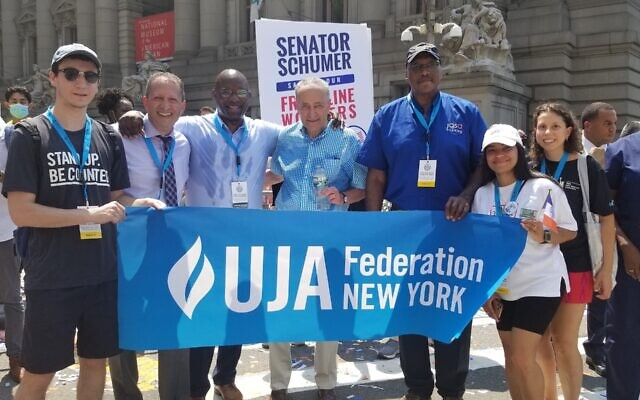 """HEROES' WELCOME: A delegation from UJA-Federation of NY and its partners -- including The New Jewish Home, JASA Seniors and Selfhelp -- marched in the """"Hometown Heroes"""" parade celebrating essential workers, Manhattan, July 8, 2021. Local politicians welcoming them included, from second to left, City Councilman Brad Lander, Rep. Jamaal Bowman and Sen. Chuck Schumer. (Courtesy UJA-Federation."""