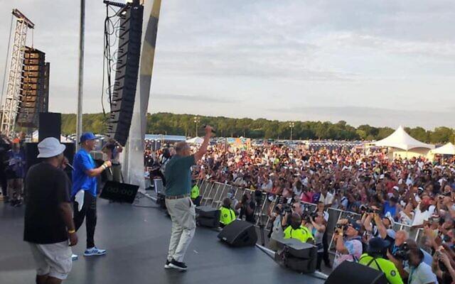"Senate Majority Leader Chuck Schumer (center) raps alongside Bronx Borough PresidentRuben Diaz Jr. (in blue shirt) at a""It's Time For Hip Hop In NYC"" concert in The Bronx, Aug. 15, 2021. (Courtesy @rubendiazjr)"