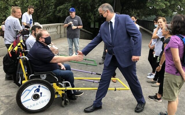 Israel Nitzan, Consul General of Israel in New York, greets a team from Friends of Access Israel during their trek in Central Park to demonstrate the need for improved access for people with disabilities, Aug. 4, 2021. (Howard Blas)