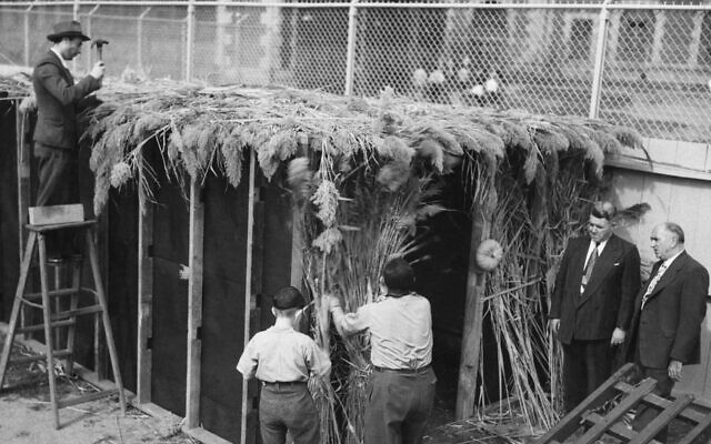 """The first sukkah built on Ellis Island is constructed by the Hebrew Immigrant Aid Society, circa 1948. Watching (right) are Robert F. Smith (on the left), """"supervisor of detention"""" at Ellis Island, and William Neubau, HIAS director on the island. This year the holiday ends Monday evening. (Photo by FPG/Archive Photos/Getty Images)"""