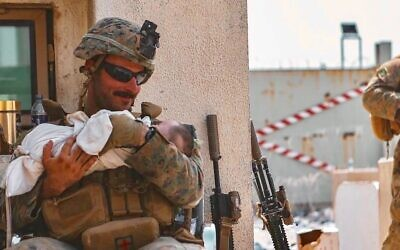 Sgt. Matt Jaffe, a U.S. Marine assigned to the 24th Marine Expeditionary Unit (MEU), holds a baby during an evacuation at Hamid Karzai International Airport, Kabul, Afghanistan, in a photo taken on Aug. 20, 2021. (Sgt. Isaiah Campbell/USMC)