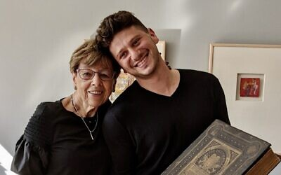 Susi Kasper Leiter and her grandson Jacob Leiter hold the 1874 family heirloom Bible that was returned to their family after being hidden during the Holocaust and discovered by the owners of a house in Germany where Jacob's great-great-grandparents were interned. (USHMM)