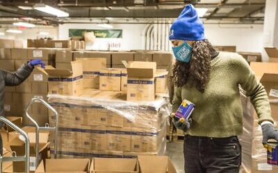 A volunteer helps package emergency food deliveries for Holocaust survivors at the Greenpoint, Brooklyn Fulfillment Center of the Metropolitan Council on Jewish Poverty, a beneficiary agency of the UJA-Federation of New York, Jan. 18, 2021. (Met Council)
