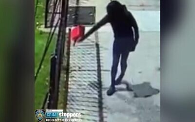 In a surveillance video, a suspect pours gasoline outside of Yeshivah of Flatbush, before lighting a match, October 14, 2021. (NYPD)