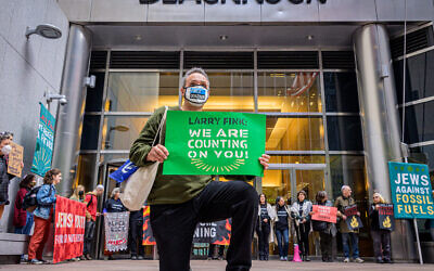 A demonstrator kneels in front of the headquarters of BlackRock in Manhattan, demanding that the investment firm's CEO Larry Fink defund the fossil fuel industry, Oct. 18, 2021. (Erik McGregor)