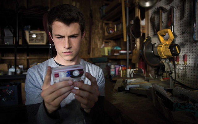 "In the Netflix series ""13 Reasons Why,"" Clay Jensen, played by Dylan Minnette, receives a box of cassette tapes recorded by Hannah Baker, a teen who committed suicide. The tapes explain who and what is responsible for her tragic death. Photo c"