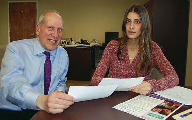 Tom Beck, executive director of JFS of Central NJ, goes over material with social worker Marilucy Lopes, who is heading up the Alzheimer's/Dementia Caregivers Support Program offered by the agency.