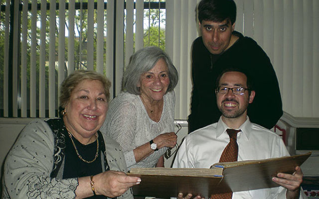 Now: Norma Fuerst Allen, second from left, joins Laura Winetsky, Rabbi Joshua Hess, and Josh Weiss (standing), going through old albums as they organize Congregation Anshe Chesed's centennial celebration.