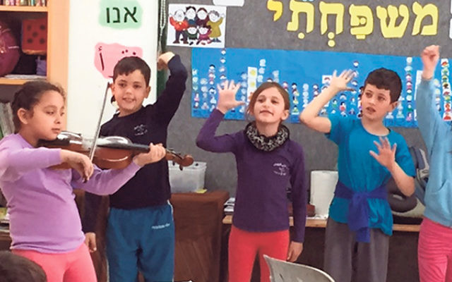 An Arab girl plays the violin as three Jewish classmates sing along at the Hand-in-Hand school in Kfar Saba.
