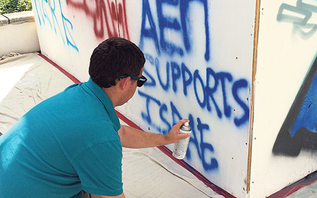 Adam Nachman of East Brunswick spray-paints his support of Israel.