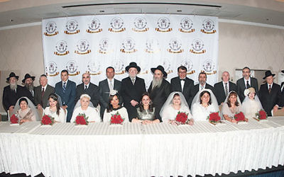 Rabbi Yisroel Meir Lau, Rabbi Mordechai Kanelsky, Shterney Kanelsky, and leaders of Bris Avrohom celebrate with the eight couples married on Sept. 14.