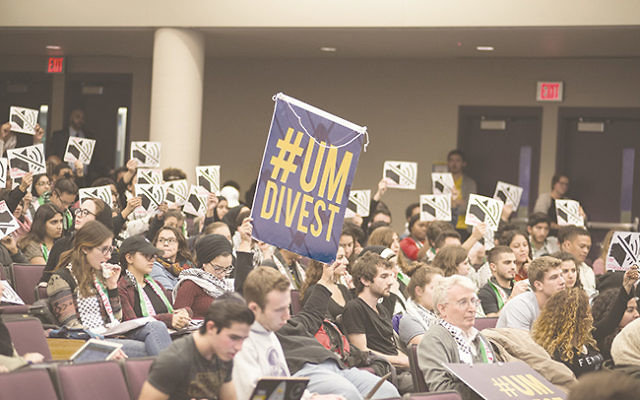 """Audience members hold signs that read """"Stop Silencing Us!""""prior to the University of Michigan student government vote on BDS."""