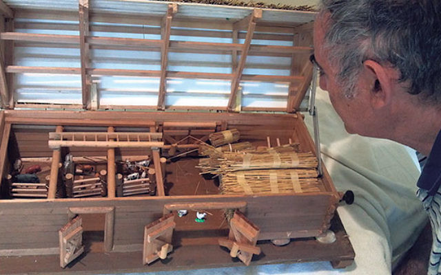 Leo Horowitz takes a close look at the model barn created by his father, Kalman. Intricate details include a stored ladder and a hiding place and escape hatch in the floor, top right.