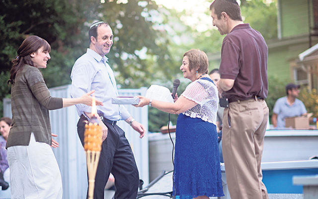 Rabbi Nasanayl and Tamar Braun, left, receive a congregational gift from Brothers of Israel copresidents Judie Boim and Andrew Samuel at the Aug. 30 barbecue celebrating the Brauns' 10th anniversary at the synagogue.