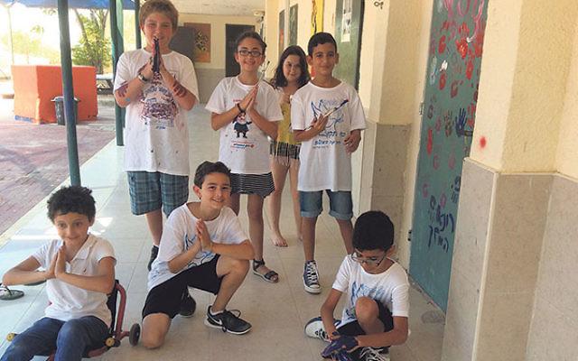 Ariel, rear, left, and Josh, bottom row, center, take part in painting the door to the yoga therapy room at the Hagiva School, with their friends in Ofakim.