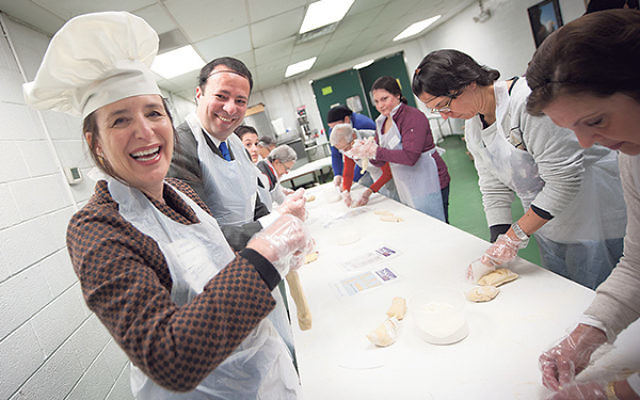 Federation president Leslie Dannin Rosenthal, left, and CEO Dov Ben-Shimon join volunteers aiming to produce over 800 loaves of hallah for the needy.