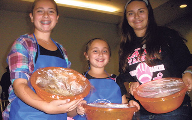 The three Genek sisters — from left, Samara, 12, Dina, eight, and Becky, 13 — came to learn the mitzva of making hallah.