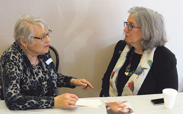 Deb Kram, the Claims Conference's client outreach manager, right, discusses Gina Lanceter's potential benefits as a child survivor of the Shoa.