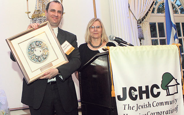 JCHC CEO Harold Colton-Max shows the award presented to him by COO Laurie Loughney at the organization's June 15 annual gala.