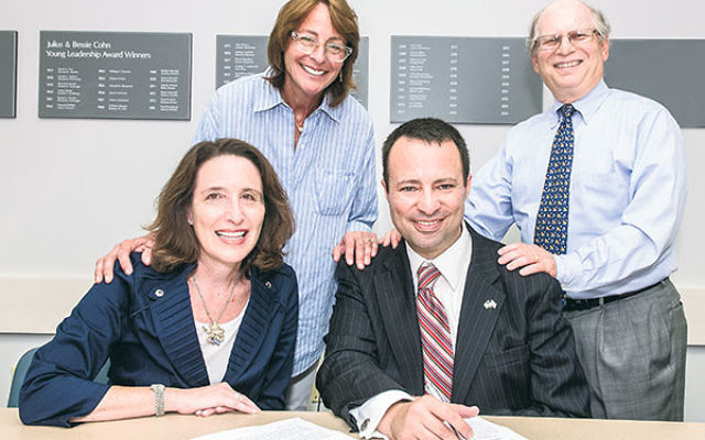 Dov Ben-Shimon signs a three-year contract to become the new executive vice president/CEO of the Jewish Federation of Greater MetroWest NJ; looking on are president Leslie Dannin Rosenthal, seated, immediate past president Lori Klinghoffer, and Ben-Shimon