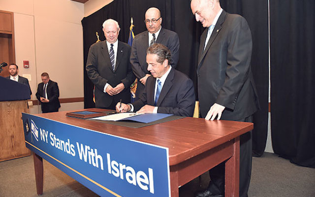 New York Gov. Andrew Cuomo signing an executive order directing the withdrawal of public funds supporting the Boycott, Divestment, and Sanctions campaign against Israel, at the Harvard Club in New York City, June 5.