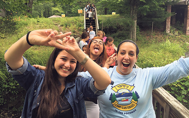 Crossing a bridge at Camp Gan Israel in the Poconos are members of the deaf program — with program director Miriam Kramer, right — Noy Balilty, left, and May Avrahami.