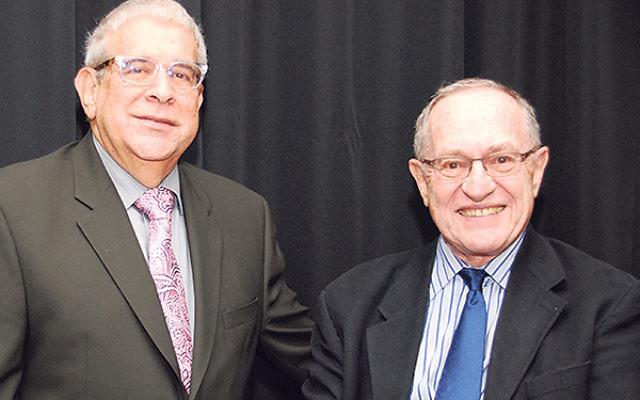 Warren Goode, vice president of Torat El, greets Dershowitz at the synagogue.
