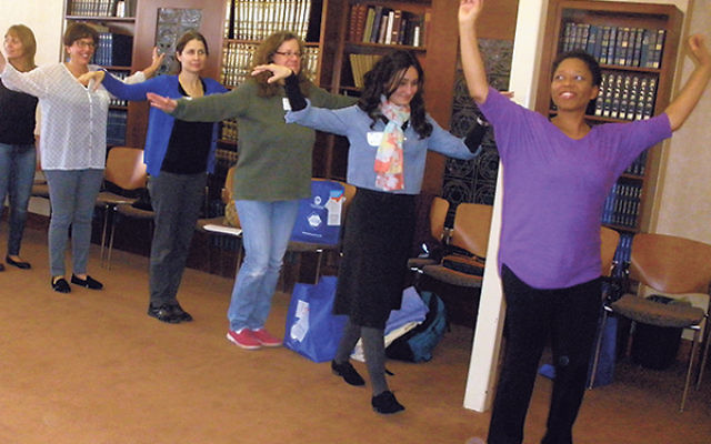"Educators flap their wings as they ""fly like beautiful butterflies"" during a workshop on how to use dance and movement to engage and interact with youngsters."