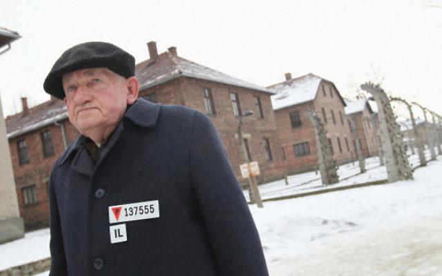 A concentration camp survivor walks through the grounds of Auschwitz in Oswiecim, Poland. Sean Gallup/Getty Images