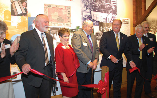 Freehold Mayor Lester Preston Jr., third from right, cuts the ribbon marking the exhibit's official opening; with him are, from left: Jean Klerman, Simon and Bella Zelingher, Rabbi Robert Fierstien, Assemblyman Eric J. Houghtaling, and Michael Berma