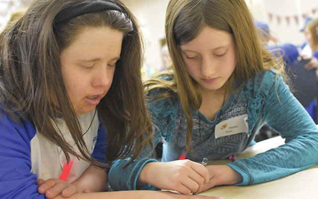 Hayley Ross of Adath Shalom, right, traces the hand of Abby Kramer, an Open Door Minyan attendee, for a decorative poster.