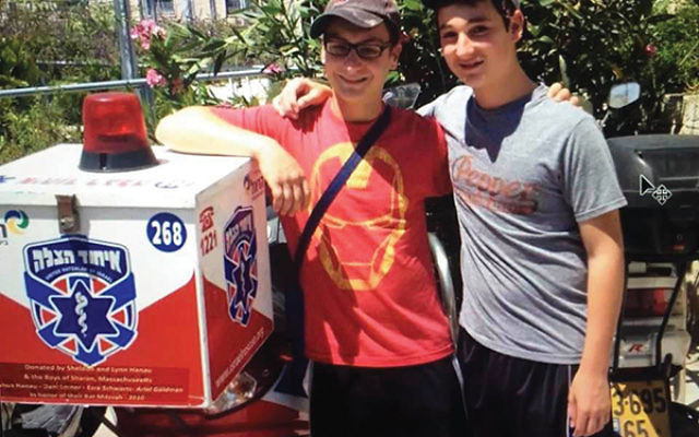 Ezra Schwartz, right, and Josh Hanau in Jerusalem in 2010 with the ambucycle that they and two other boys donated to United Hatzalah as part of their shared bar mitzvah project. Photos Courtesy of Ruth Schwartz