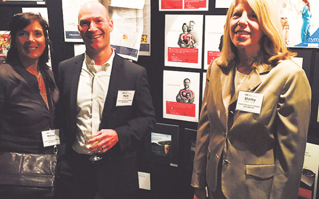 With some of their award-winning ads are, from left, Melissa Simon, Mark Berkley, and Shelley Labiner.