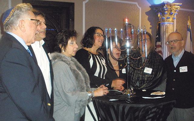 Lighting the menora are federation board members who were among those who oversaw the merger, from left, Ken Philmus, Joe Hollander, Elise Feldman, Adrienne Ross, Marilyn Goldsmith, Mitch Frumkin, Sheryl Grutman, and Murray Katz.