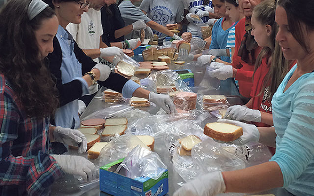 "Volunteers make sandwiches in the Temple Emanu-El kitchen in the 13th year of the late Mandy Reichman's ""Bags of Love"" program."