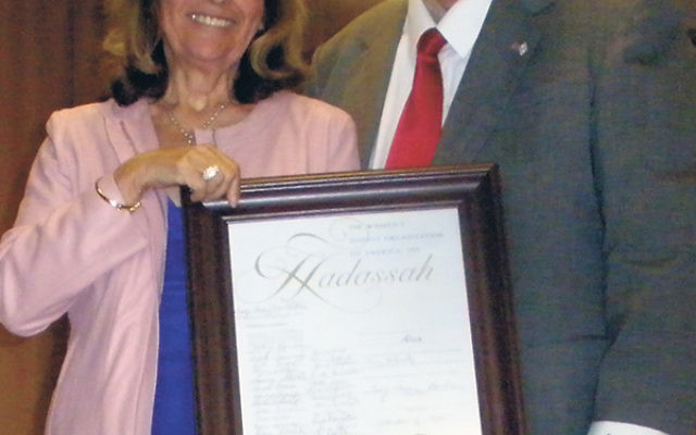 Tiby Lapkin, charter president of the Alisa chapter of Hadassah, presents Stephen Flatow with a copy of the group's original charter, which he signed. The chapter was named in honor of Flatow's daughter, who was killed in a terrorist bombing i